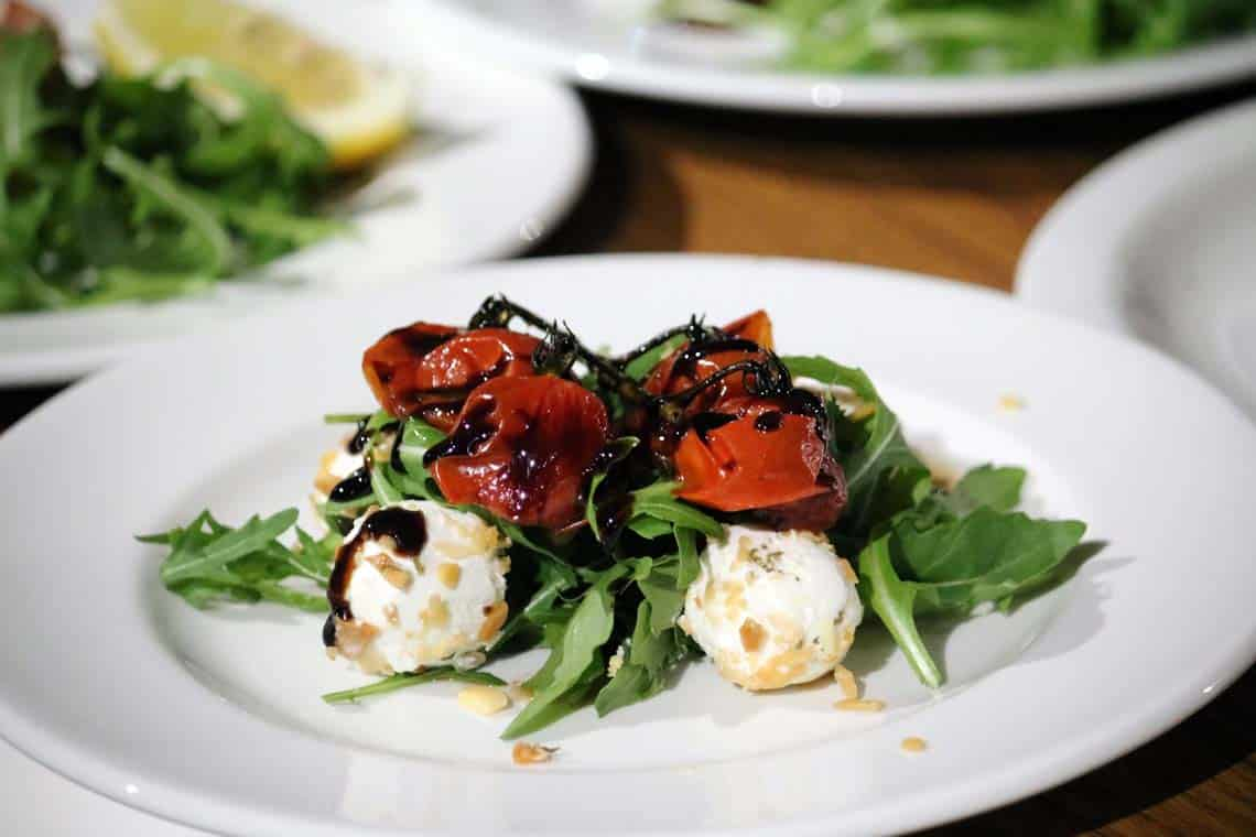 Almond Rolled Goats Cheese on Roquette, Roasted Cherry Tomatoes